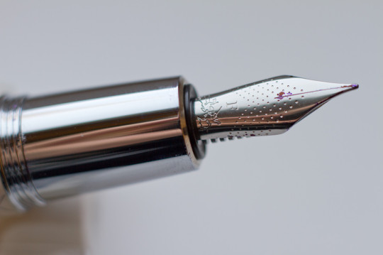 The laser-etched Parquet pattern on the fountain pen. There is no etched logo. The logo is embossed on the cap.