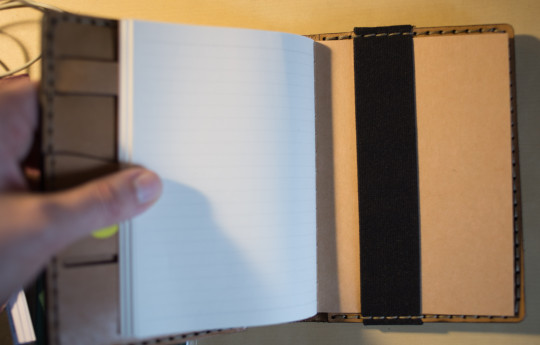 The main notebook is held by an elastic band